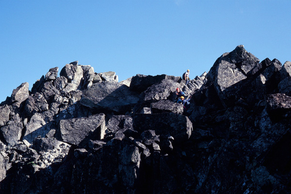 Bill, Gary, and Doug climb over large rock blocks to the summit of Sloan Peak