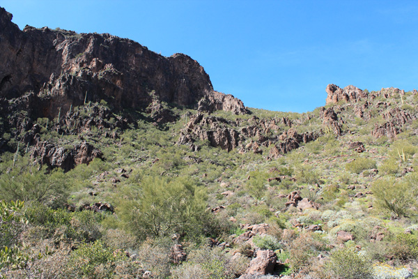 The trail passes through the rocky band to an upper saddle just out of view above