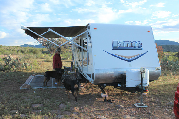 Linda, our dogs, and our trailer at our dispersed campsite in morning light.