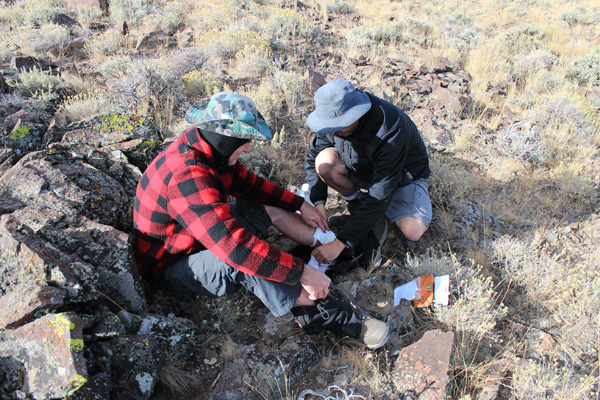 Michael and John clean and bandage Michael's leg injury on Mickey Butte's summit.