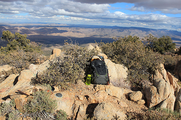 The Peacock Peak summit with registry bottle and benchmark below to the left