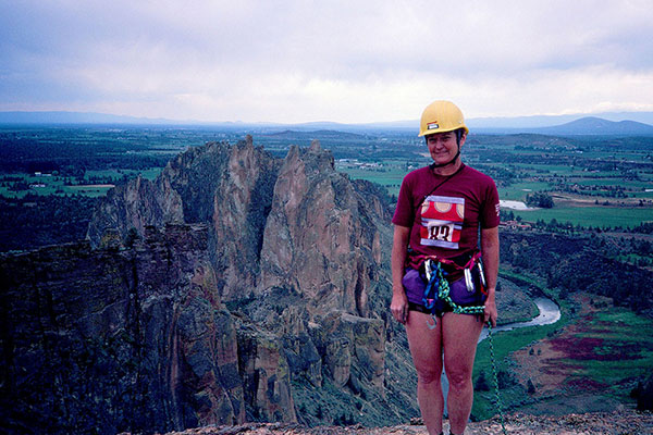 Linda at the top of Monkey Face. The Smith Rock Group of cliffs, the Crooked River, and the Oregon Cascades lie behind her.