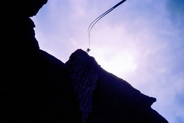 Linda starts her free rappel off Monkey Face above me. The breeze blows the rope about.